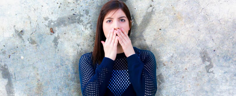 Image of a woman covering her mouth showing body language basics.