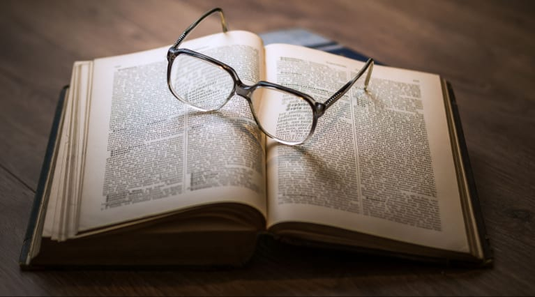 A book with a pair of glasses sitting on top