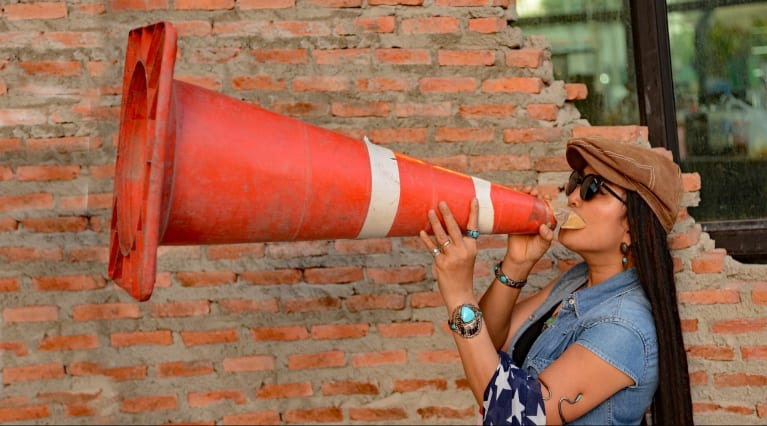 Woman using a cone as a loudspeaker
