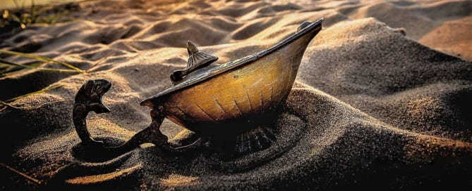 A magic lamp half buried on a beach