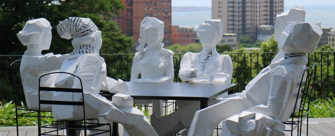 Statues of people sitting around a table