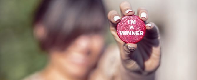 Woman holding a badge stating I Am a Winner