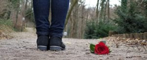 Sad ending - person standing with abandoned rose on the ground