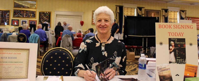 Author Rita M. Boehm at a book signing table